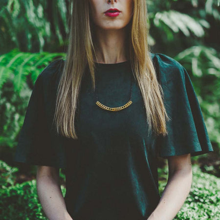 Gold geometric necklace on lady with green dress.