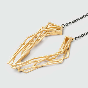 Gold geometric pendant with chain necklace.