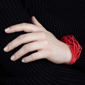 A large cuff bracelet in coral red.