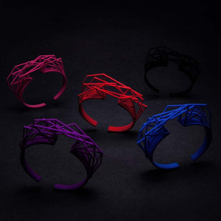 Large cuff bracelets in different colors falling.