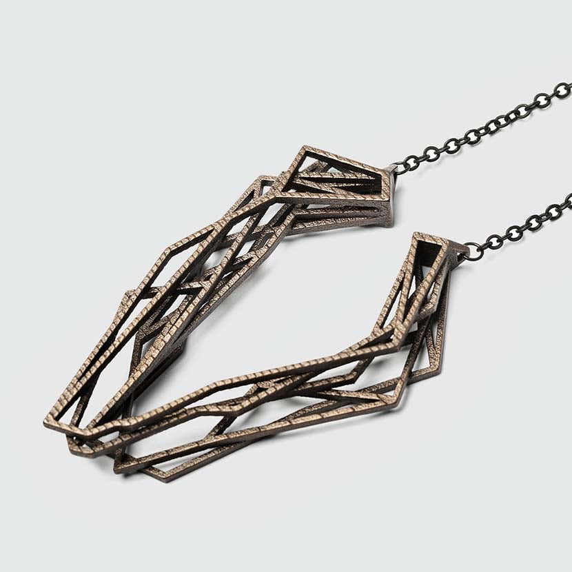 Long bronze necklace with geometric pendant.