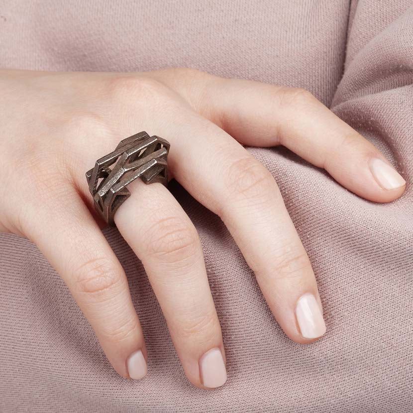 Modern bronze ring on finger of woman.