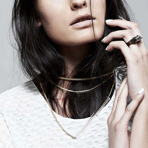 Dark haired model wearing a modern bronze ring.