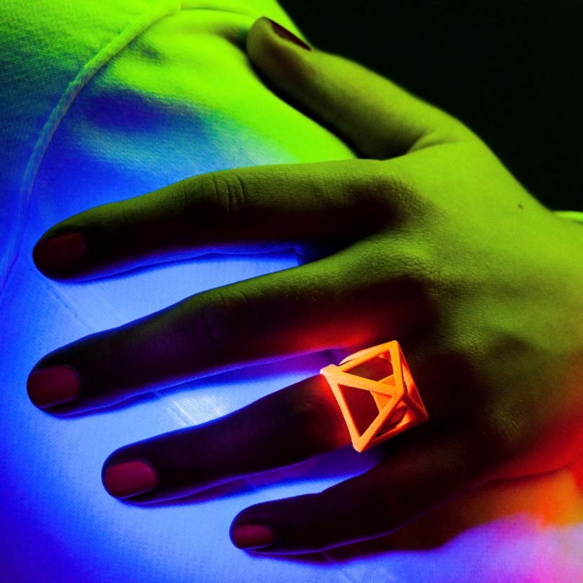 Neon orange jewelry with woman's hand.