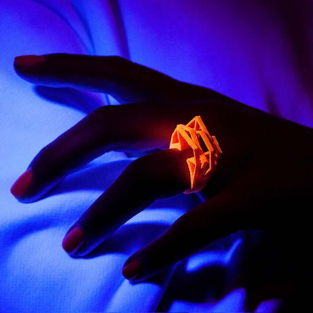 Stylish neon orange ring shown under black light.