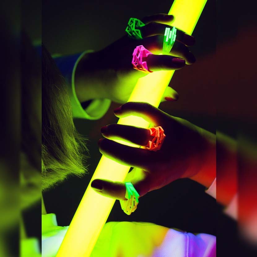Lady with neon orange rings posing with light sword.