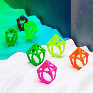 Pink pyramid ring together with green, yellow and orange rings.