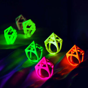 Pink pyramid ring in a group of colorful uv jewelry.