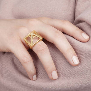 Pyramid ring held by woman.