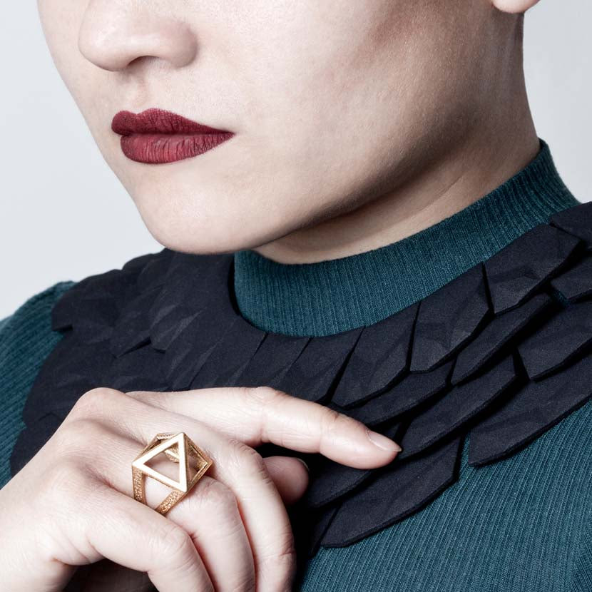 Pyramid ring on finger of woman wearing an Egypt collar necklace.