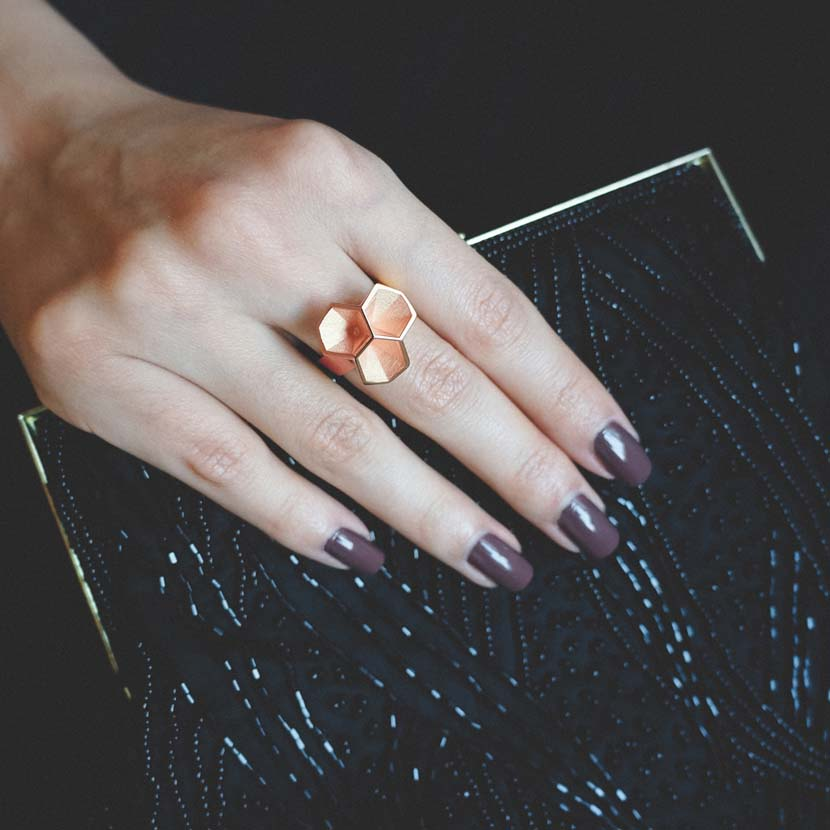 Rose gold honeycomb ring on finger in front of a nice bag.