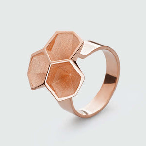 Rose gold honeycomb ring with facets.