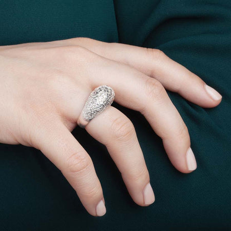 Silver dome ring on a hand.