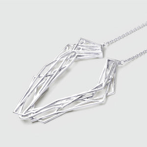 Silver geometric necklace with intricate design.