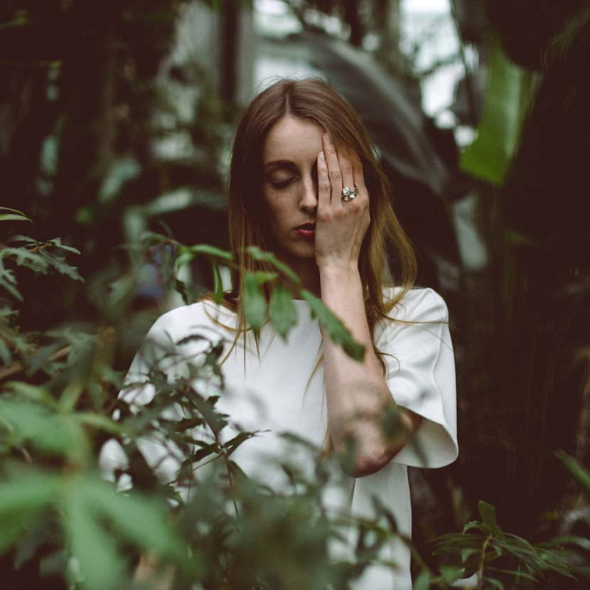 Silver honeycomb ring on hand of woman in between plants.