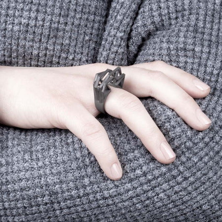 Statement ring titanium displayed by woman.