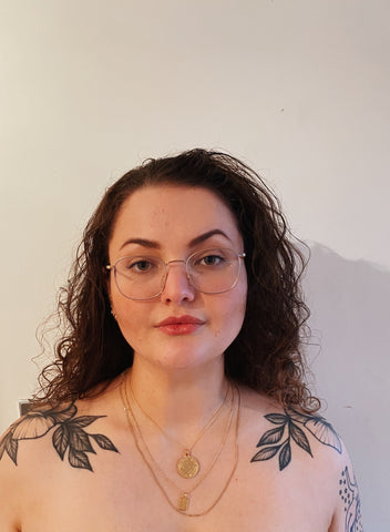 Becca is standing against a plain white wall with her shoulder tattoos on show.