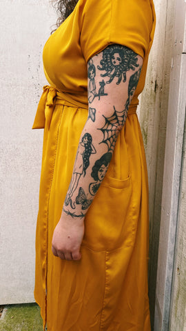 Becca is standing sideways to show the sleeve of tattoos on her left arm.