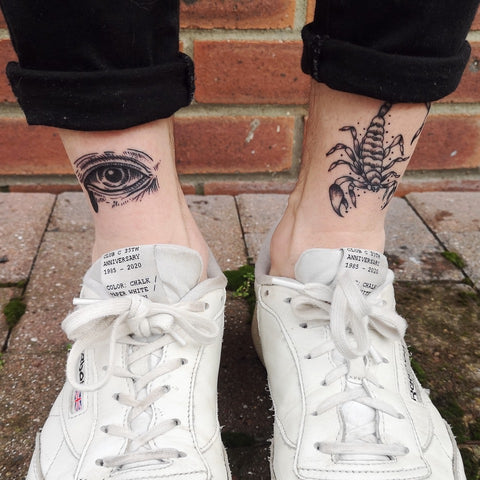 An eye and a scorpion have been tattooed on the front of a client's ankle in fine black linework.