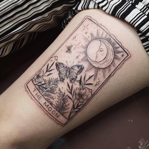 The image shows The Moon tarot card tattooed in fine black ink on a client's leg.