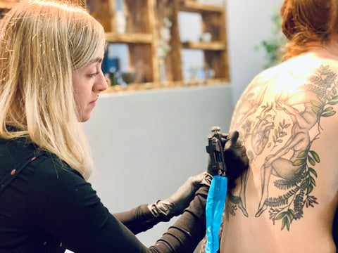 Frances is sitting down and tattooing a large design on a client's back.