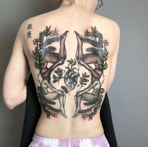 Four women's bodies with foliage are seen tattooed on a client's back.