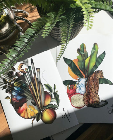 Frances' illustrations of botanicals are laid out on a table with partial sunshine on them.