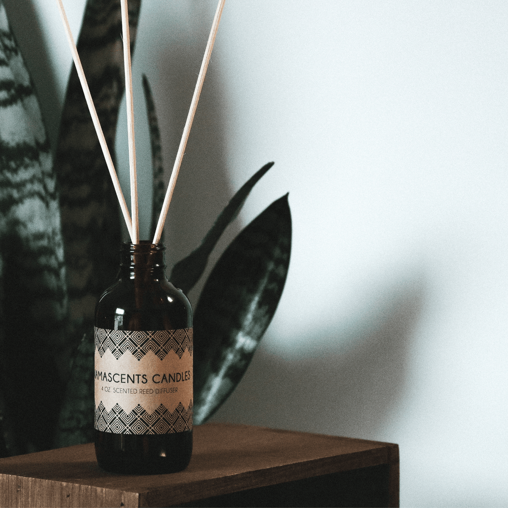 REED DIFFUSER bottle with reeds inside bottle sitting in front of plant on a wooden box