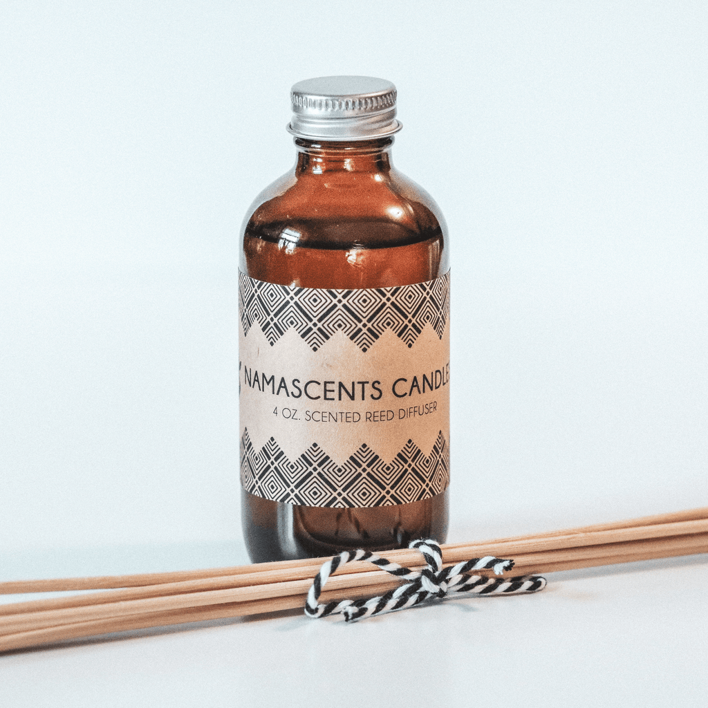 REED DIFFUSER bottle with reeds tied in black and white twine on white background