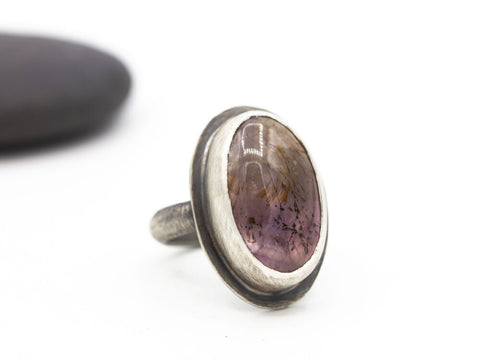 Transparent cacoxenite in amethyst oval cabochon set in sterling silver on a half-round sterling band. Size 6.5