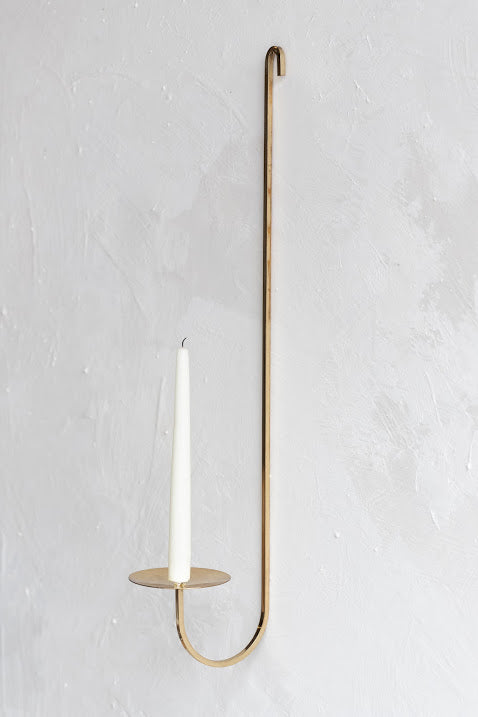 Long skinny brass sconce with a white taper candle on a plaster wall. Side view.
