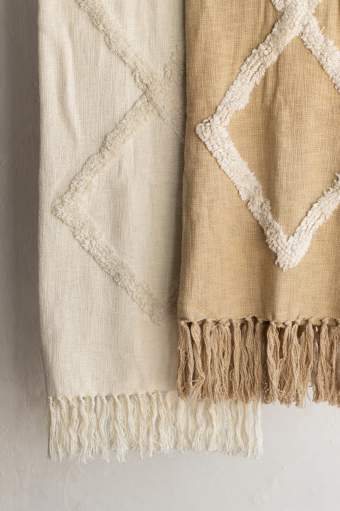 Two hanging blankets with a tufted diamond pattern. One is cream and one is light brownish yellow.