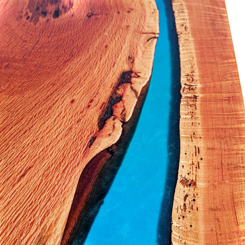 river table top made with deep pour clear epoxy resin. Sheoak slabs with blue turquoise resin flowing between