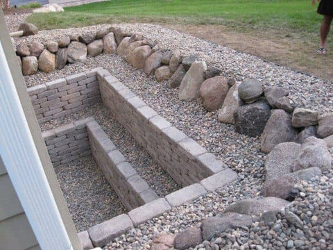 Square tiered stone walls in an egress window well
