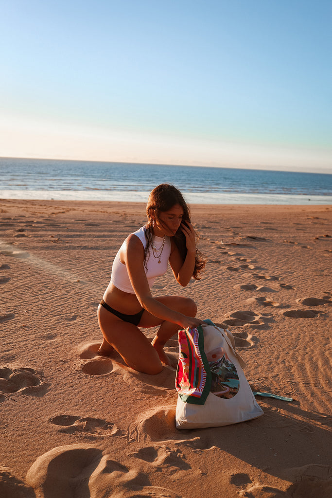 girl getting stuff out of tote bag with scarf on beach