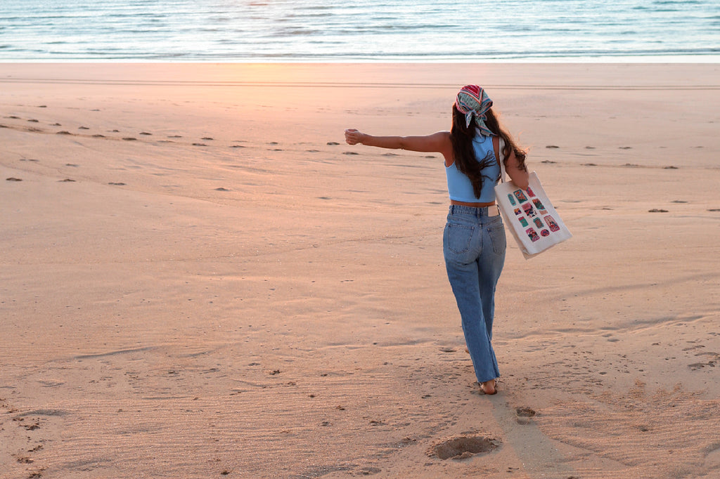 girl with arm out from behind wearing scarf and tote bag on beach
