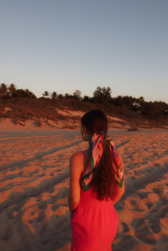 22 girl on beach at sunset with scarf tied in her hair wearing a pink dress