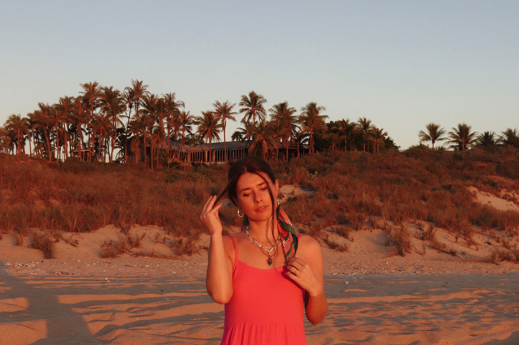 24 girl playing with hair wearing pink on beach palm trees in background copy
