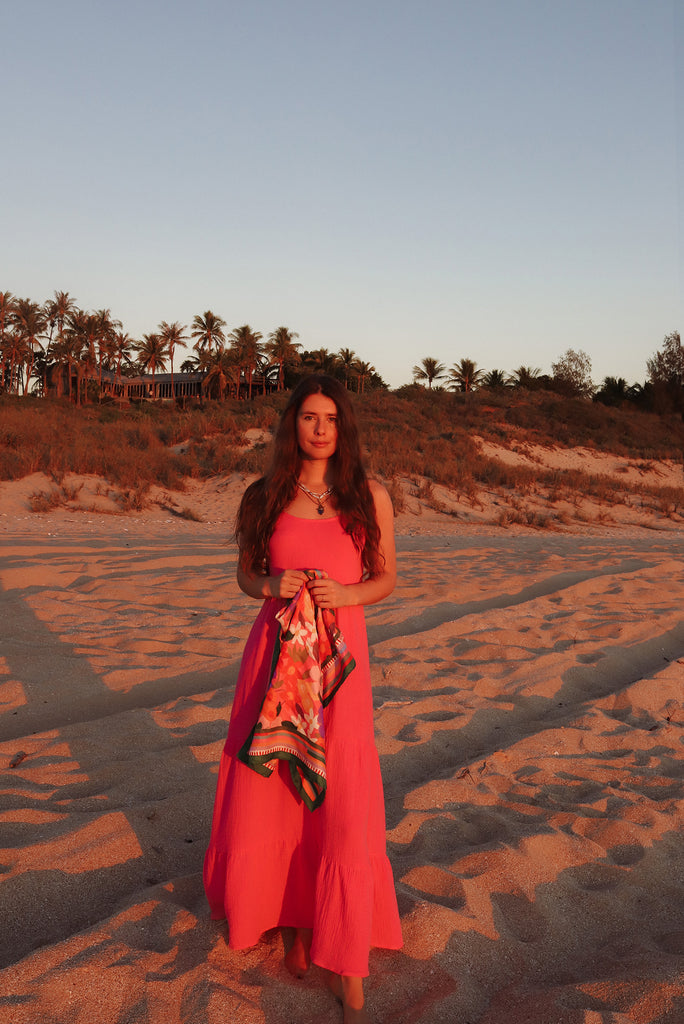 25 girl on beach at sunset wearing pink holding scarf