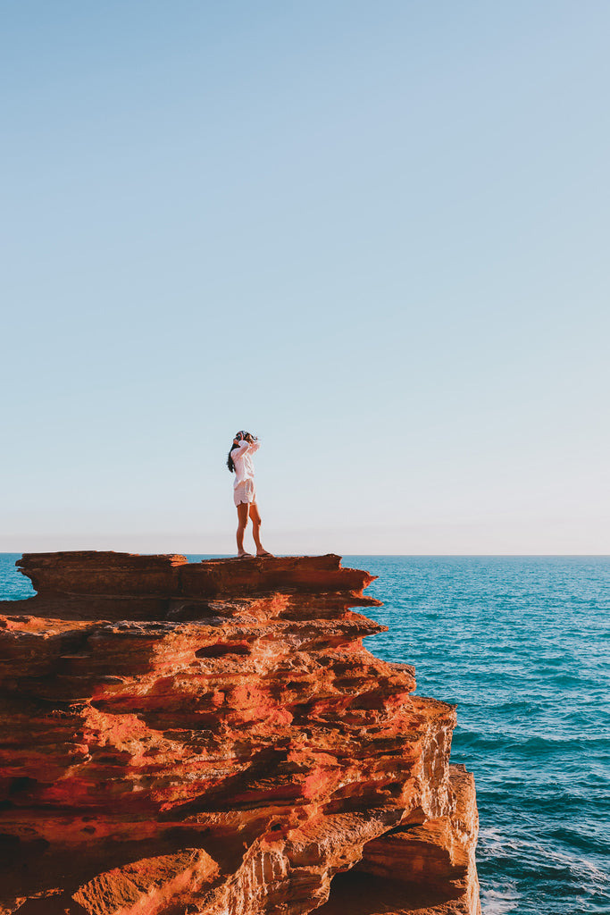 29 girl standing on red cliff