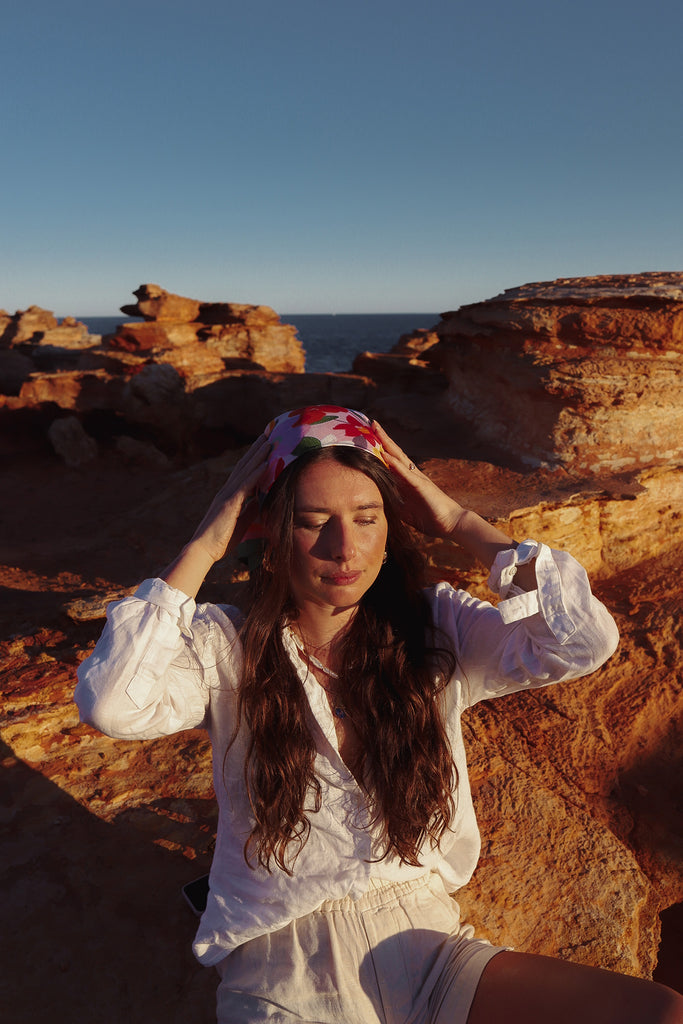 girl sat on red cliffs face on touching scarf on head