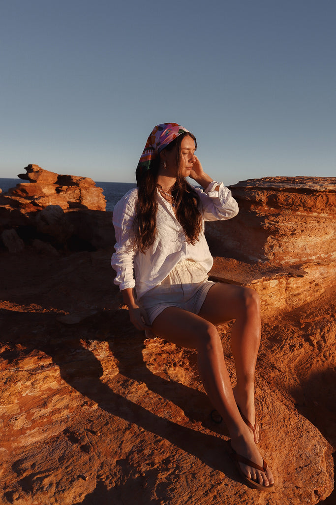 girl sat on red cliff full body with head turned wearing scarf on head bandana
