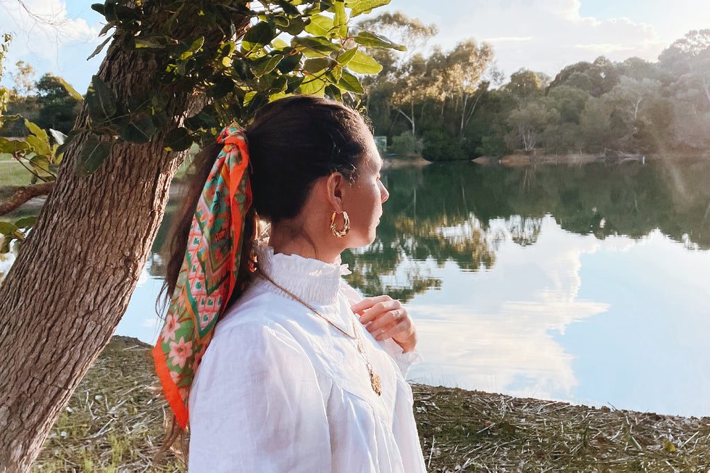 girl facing away looking at lake with scarf and earring