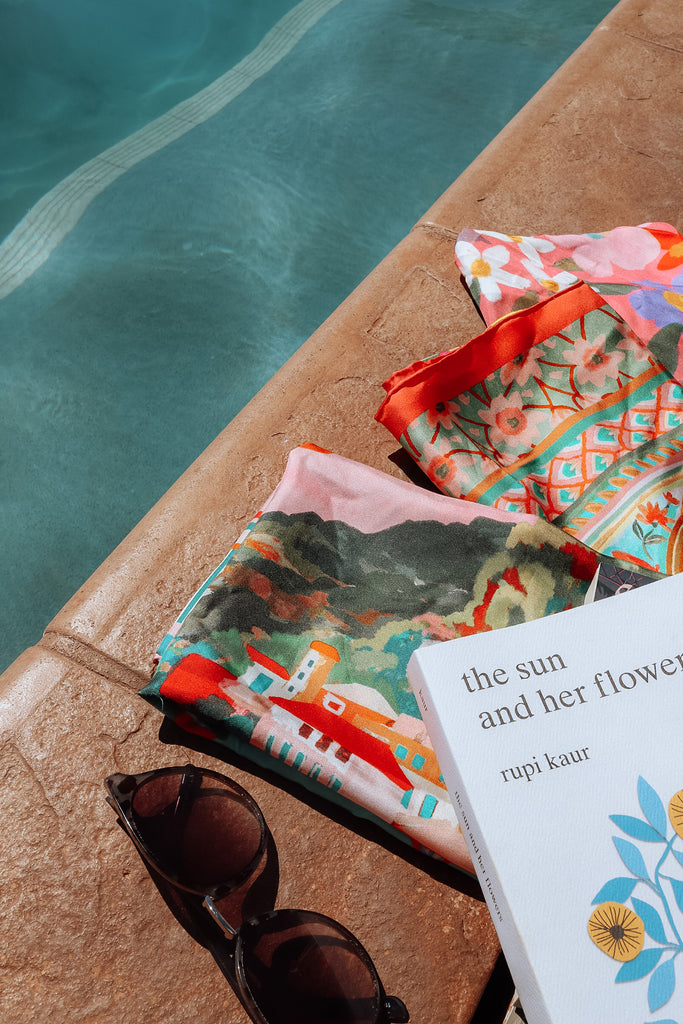 close up of folded scarves silk scarf by pool with book