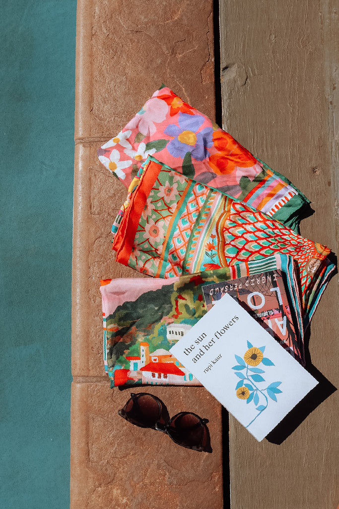 folded scarves 3 silk scarves with book by pool