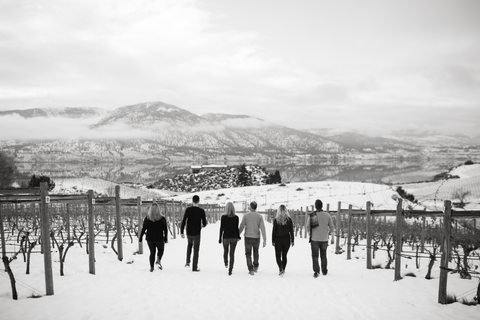 Black & white photo of Smith family walking away from the camera in snowy vineyard