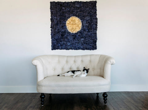 makira moon panel displayed behind couch with cat on it