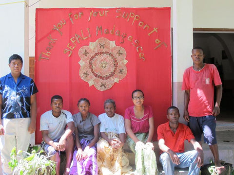 SEPALIM team members standing with a handmade banner that says thank you
