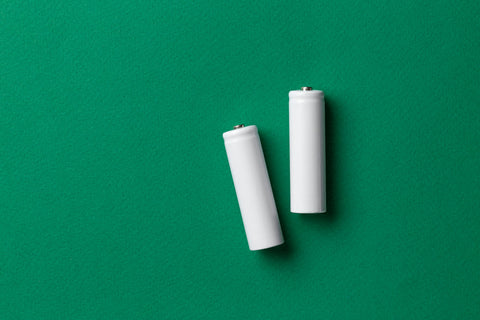AAA batteries on green background