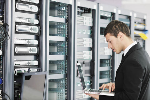 young IT engineer in data server room